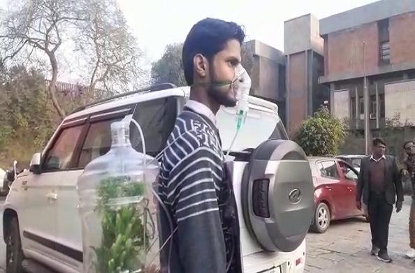 प्रदूषण कम करने के लिए दिनेश की पहल…ऑक्सीजन मास्क लगाकर किया लोगों को जागरुक